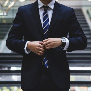 Photo of a man doing up a suit jacket