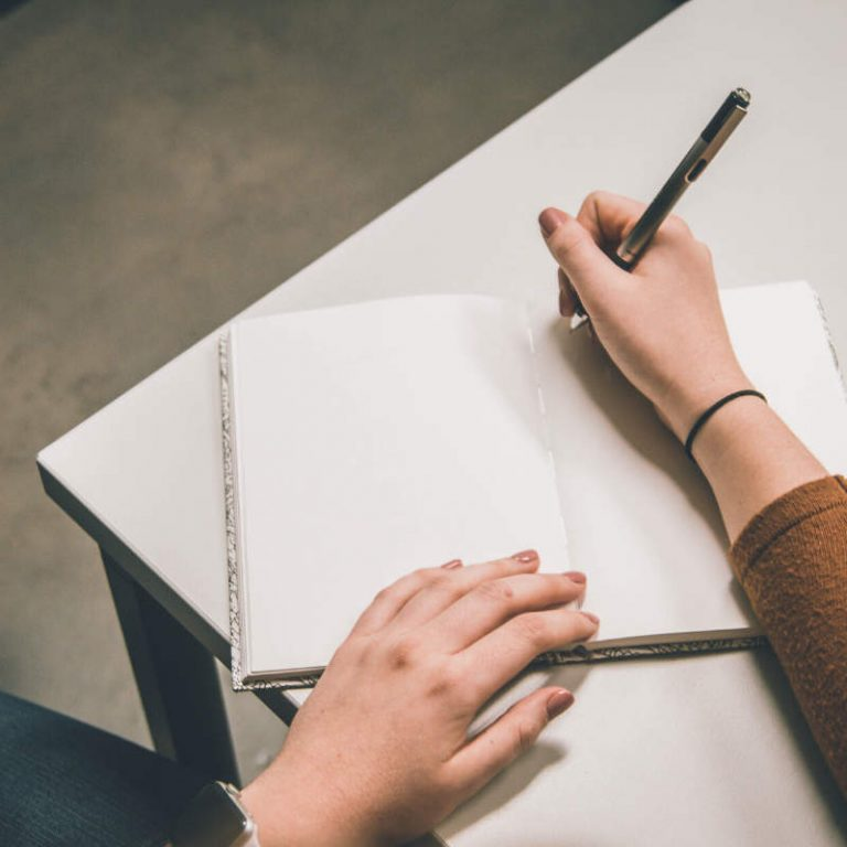 Photo of a person writing in a blank notebook