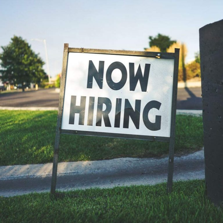 """Photo of sign saying """"Now Hiring"""""""