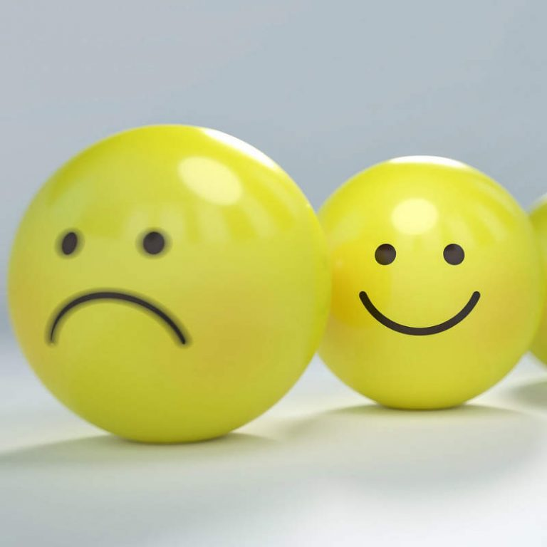 Photo of 2 yellow balls, one with a smiley face and the other sad