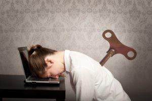 Lady slumped at laptop computer with large wind up key in her back