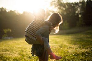 Child having a piggyback at sunset
