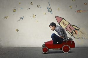 Man sat in child's toy car with a hand-drawn rocket on the wall behind him