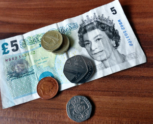 British currency on table consisting of £5 note and loose change