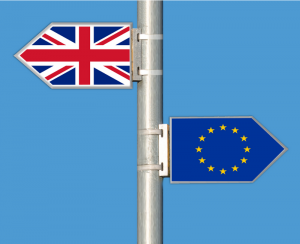 Sign post with Union Jack flag pointing left and EU flag pointing right