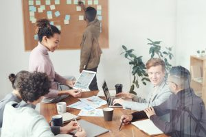 Photo of a group of people talking at a desk