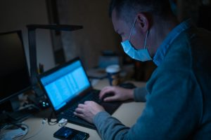 Photo of a man at a laptop in a face mask