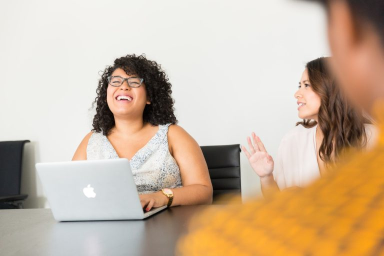 Photo of woman laughing in front of a laptop