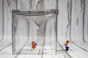 2 toy figures, one inside a glass