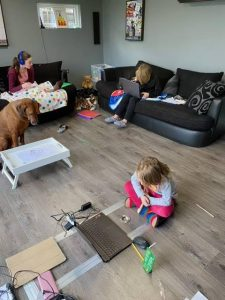 living room with three children and a dog home schooling during lockdown for the covid pandemic